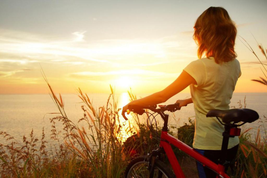 девушка с велосипедом смотрит на закат