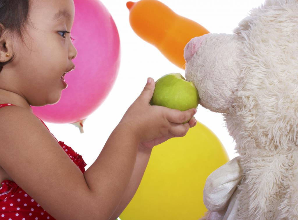 girl feeding apple dog toy