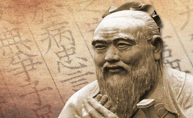 Statue of Confucius on the background of hieroglyphs